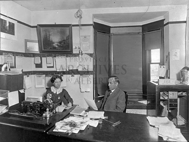 A2595 - View of the interior of the Edmonton City Dairy Office showing an unidentified woman and Warren W. Prevey seated at a desk.  - ca 1911